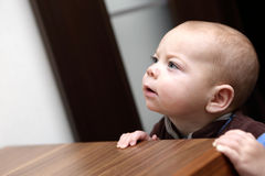Curious baby boy and a chest of drawers Stock Photo