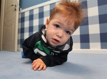 A curious baby boy lying on a floor in room Royalty Free Stock Photo