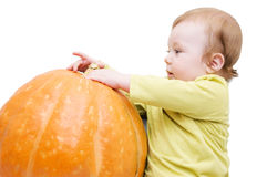 Curious baby boy playing with pumpkin Royalty Free Stock Images