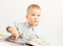 Curious baby boy studying with the book Royalty Free Stock Photo