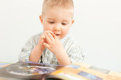 Curious baby boy studying with the book. This image has attached release Stock Images