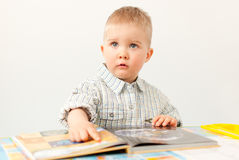 Curious baby boy studying with the book Royalty Free Stock Images