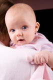 Curious baby on fathers shoulder. Open eyes, open mouth, toy in hand stock image