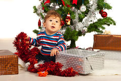 Curious baby  in front of Christmas tree Royalty Free Stock Photos