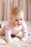 Curious baby girl crawling on bed, closeup shot Royalty Free Stock Photos