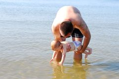 Curious baby girl with her father touching the sea Stock Photos