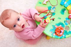 Curious baby girl playing with developing wooden toy. Curious infant baby girl playing with developing wooden toy Stock Image