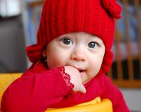 Curious baby girl with red cap. Seven months old curious baby girl with red cap and red blouse inside the house Stock Photo