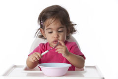 Curious baby girl is testing her fork Stock Images