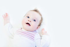 Curious baby girl in a white knitted dress Stock Images