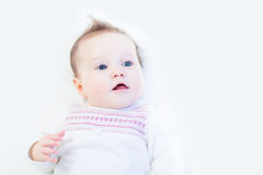 Curious baby girl in a white knitted dress Royalty Free Stock Photo