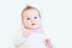 Curious baby girl in a white knitted dress Royalty Free Stock Photos
