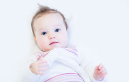 Curious baby girl in a white knitted dress Royalty Free Stock Images