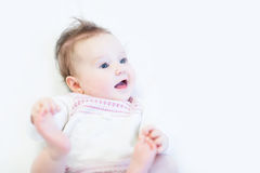 Curious baby girl in a white knitted dress Stock Photo
