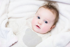 Curious baby in a knitted sweater Stock Image
