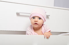 Curious baby looking out of the chest of drawers. Portrait of a curious baby looking out of the children's chest of drawers Stock Images