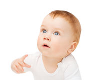 Curious baby lying on floor and looking up Royalty Free Stock Image
