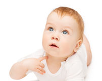 Curious baby lying on floor and looking up Royalty Free Stock Images
