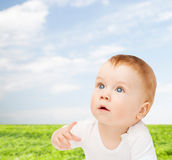 Curious baby lying on floor and looking up Stock Photos