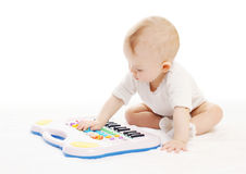 Curious baby playing with toy piano Stock Images