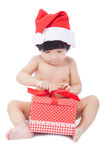 Curious  baby in Santa cap looking at giftbox Stock Photography