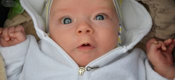 Curious baby in a stroller. Three months old boy laying in a pram is little bit surprised by a photographer. He shows his big and beautiful blue eyes Stock Photo