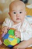 Curious baby with a  toy. A chinese curious baby with a toy Stock Images