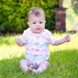 A curious baby in a vest sitting on the grass in the garden Royalty Free Stock Photo