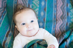 Curious baby in a warm green blanket Royalty Free Stock Photos