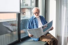 Curious bearded pensioner reading newspaper on windowsill Stock Photo