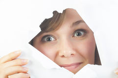 Curious beautiful woman looking through the hole in paper Royalty Free Stock Photo