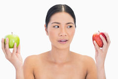 Curious black haired model holding apples in both hands Royalty Free Stock Image