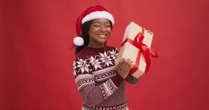 Curious black lady in santa hat shaking gift box, enjoying Christmas holiday, red background