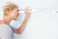 Curious blonde woman looking through venetian blind Royalty Free Stock Images
