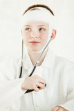 Curious boy with bandaged head taking his pulse Royalty Free Stock Photos