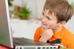 Curious boy with computer Stock Photo