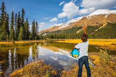 Curious boy with a globe under his arm Royalty Free Stock Image