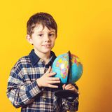 Curious boy holding earth globe map. Little traveler, isolated on yellow. Kid exploring the new horizons at globe. Funny kid with. Globe. Back to school concept royalty free stock photos
