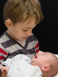 Curious Boy holding his little brother Royalty Free Stock Image