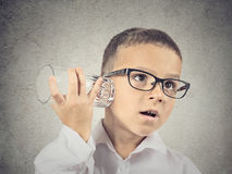 Curious boy listening with glass cup to a conversation. Closeup portrait, headshot curious nosy child using a glass as telephone listening to conversation Royalty Free Stock Image