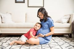 Curious Boy Listening To Mother`s Pregnant Tummy. Curious boy listening to pregnant mother`s tummy in at home royalty free stock photo