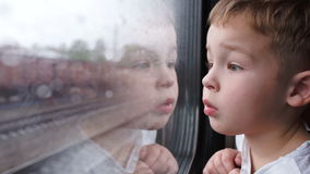 Curious boy looking out of the train window in. Close-up shot of a little curious boy looking out of the window in train. It's raining outside, child reflecting stock footage