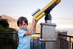 Curious boy, looking through a telescope at something interestin Stock Image