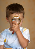Curious boy with magnifying glass Stock Photography