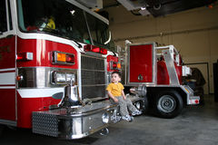 Curious Boy Sitting On A Fire Truck Stock Photography