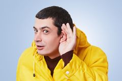 Curious brunet male model tries to overhear something, keeps hand on ear, listens gossips in next room, wears yellow anorak, isola royalty free stock images