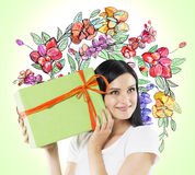 A curious brunette woman tries to guess what is inside the green gift box. Royalty Free Stock Photos