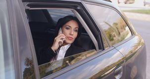 Curious business woman on phone looking from car stock video