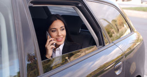 Curious business woman on phone looking from car Stock Image