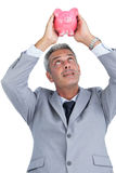 Curious businessman holding piggy bank above his head Stock Photography